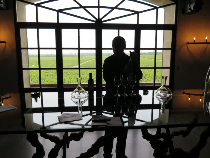 Radiant light casts dramatic shadows across Pontet Canet's tasting room as Jean Michel Comme, in silhouette, moves to pour the 2009 wine into a crystal decanter. Photo : Frank Ward.